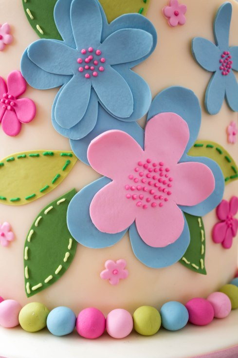 Modelling paste hand cut flowers in blue and pink with cutters used for the small and very small flowers with hand cut modelling paste leave finished with royal icing piped stitching